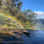 A rainbow atop the Waterfall on a sunny day.