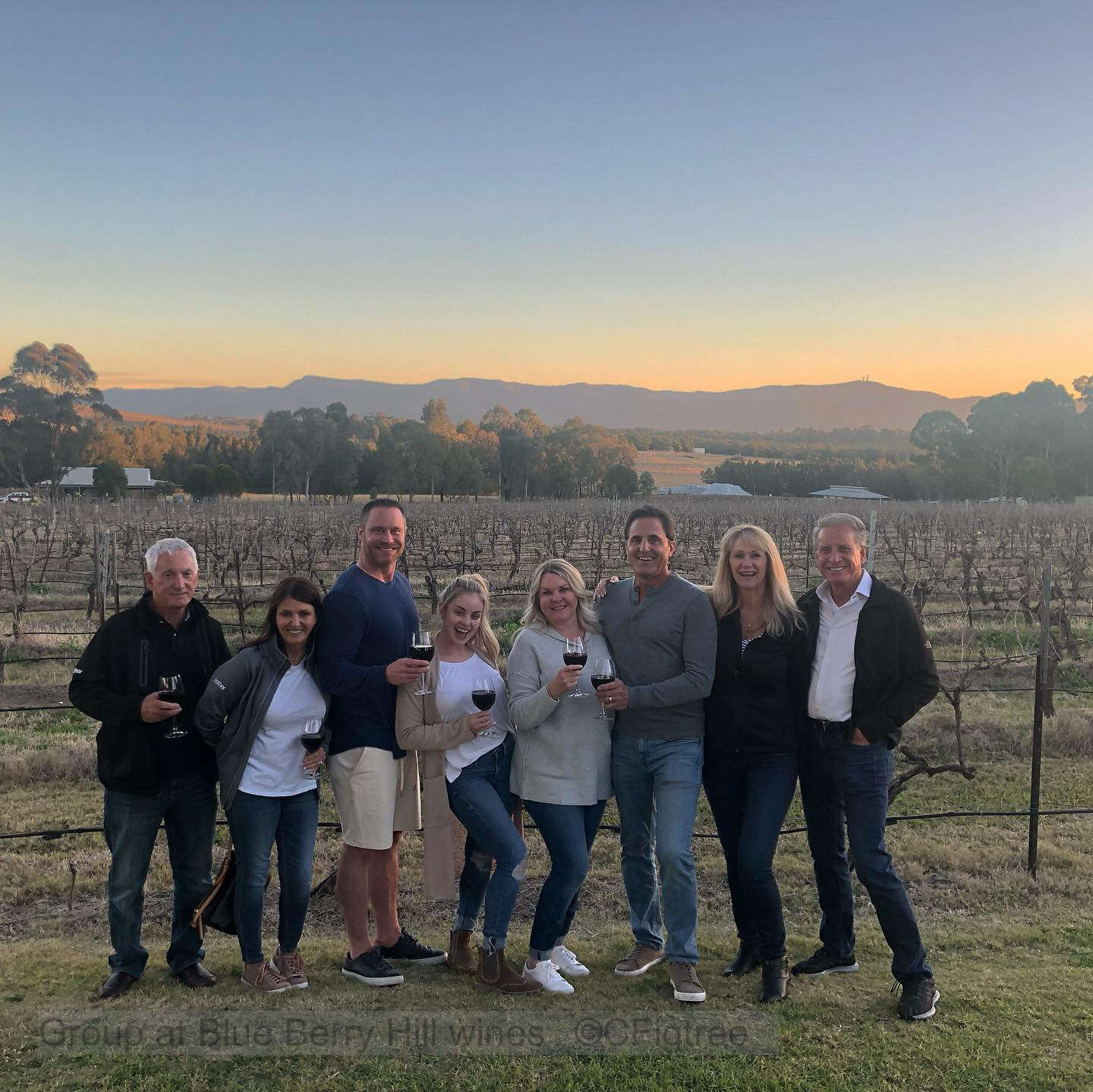 A Group at Blue Berry Hill wines at unset with vineyard in the background