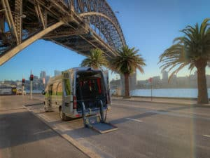Sydney Adventure Tours Sprinter fitted with wheelchair lift. Parked near the south pylon of the Sydney Harbour Bridge.